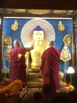 Lama Gelek (l) and Tashi Tsering (r) help to paint the Buddha statue.