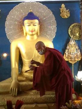 Karma Wangchuk touches up the golden Buddha.