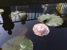 Life-like pink lotus made of wax butter in water with lily pads.